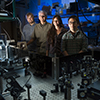 Jordan Dood, Bern Kohler, Ashley Beckstead, and Tom Zhang, from left, are photographed in Kohler's laboratory at Montana State University in Bozeman.  In front of them is the laser instrument that was critical for their newly published findings about DNA and UV radiation. (MSU photo by Kelly Gorham).