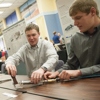 Two College of Engineering seniors, Eric Mower, at right, and Daniel Hurst demonstrate the working model of their automatic cattle tattooing plier Thursday during Montana State University's Engineering Design Fair. The device will be employed by an area veterinarian to designate that cattle have received the brucellosis vaccination. MSU Photo by Sepp Jannotta.
