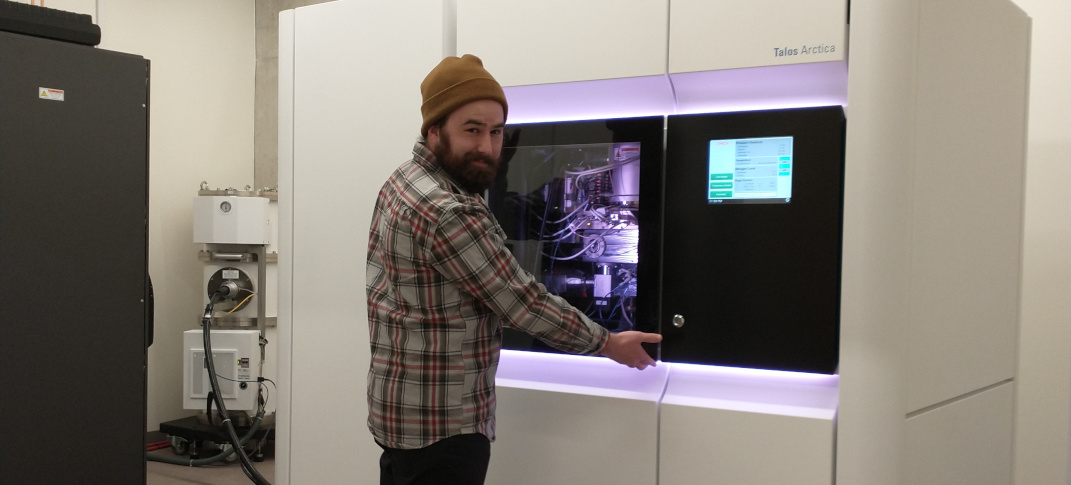 A graduate student posing in front of the completed Talos Arctica