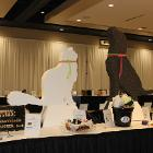 Image of white cat and black dog sculptures on table.