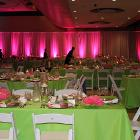 Image of squre table with green tablegloth and white chairs with staff setting up for event in the background. Walls are lit with magenta floor lights.