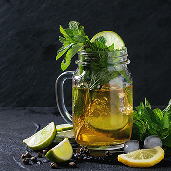 bevereage in a glass container with lemon slices and mint
