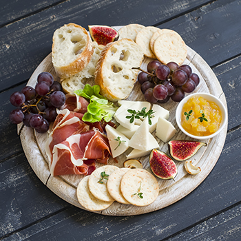 charcuterie platter with sliced bread, meat, cheese, and fruit