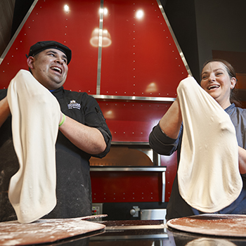 two staff members making pizza dough