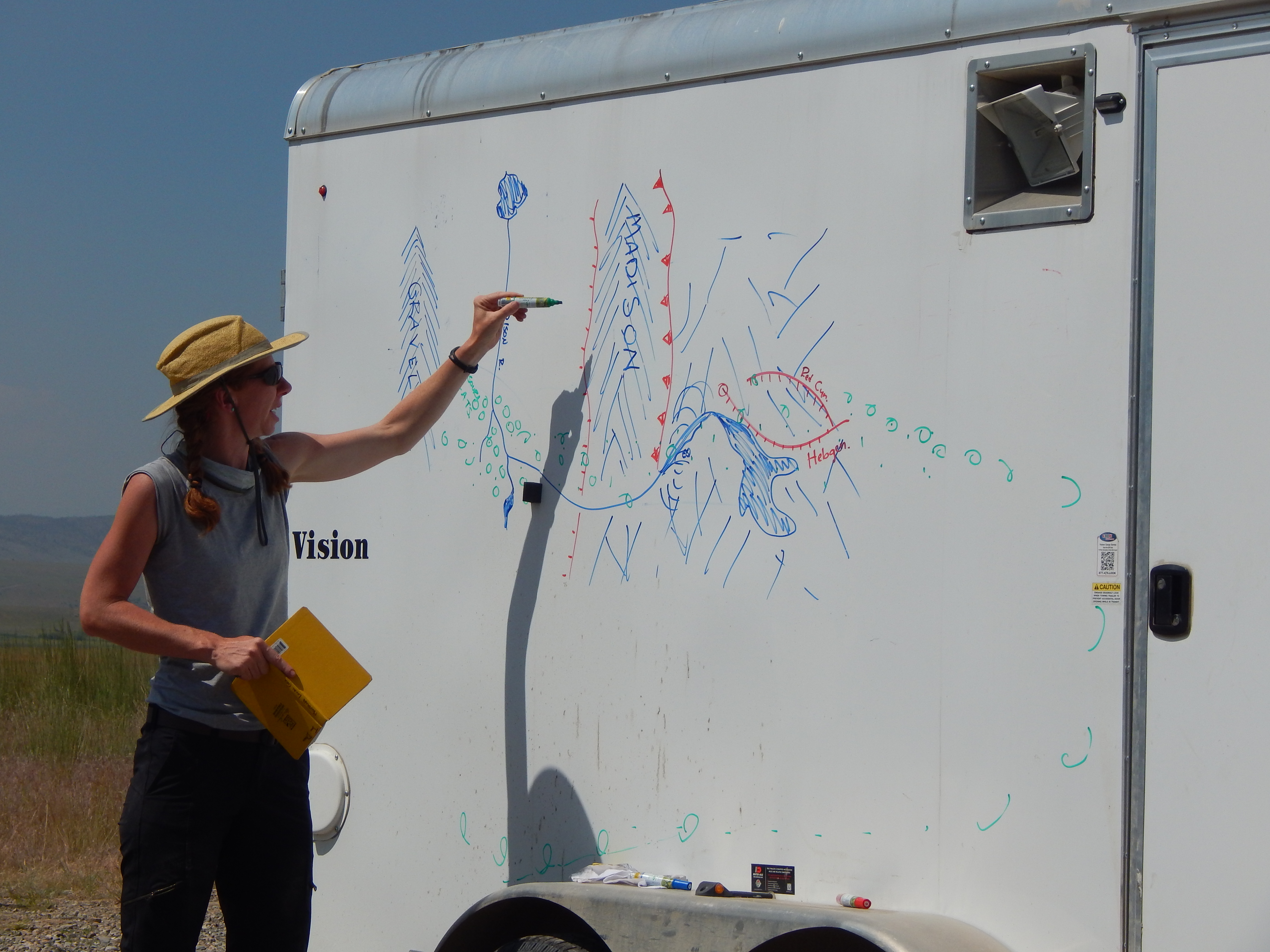 Dr. Jean Dixon delivering a lecture in the field using a trailer as a white board