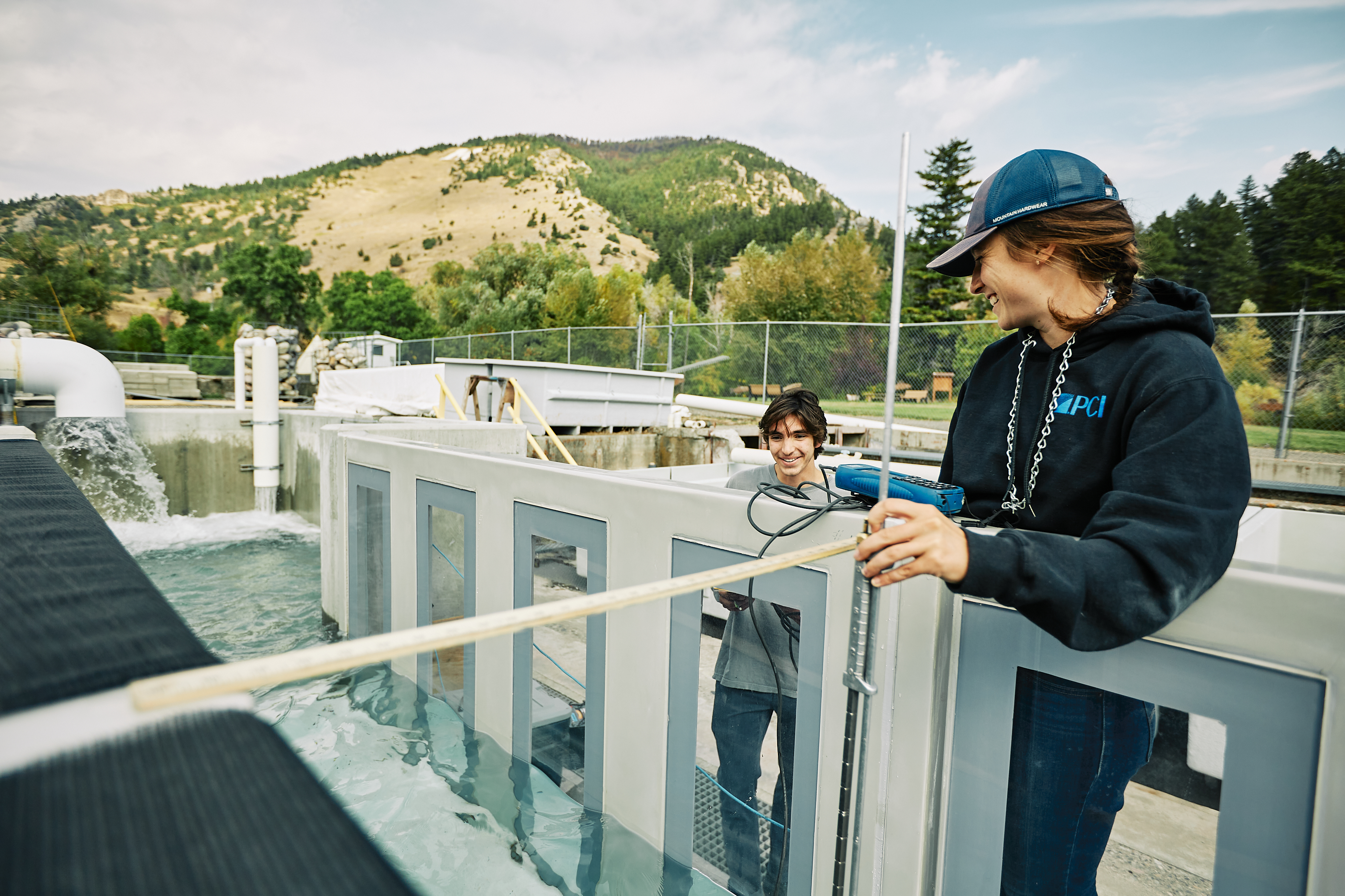 Megan and Anthony, students at Montana State University, take measurements at the outdoor flume at the Bozeman Fish Technology Center