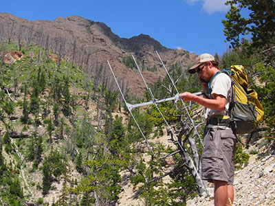 student listens to radio antenna while tracking in mountains