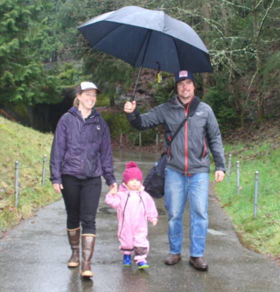 Chris walking in the rain with wife and daughter