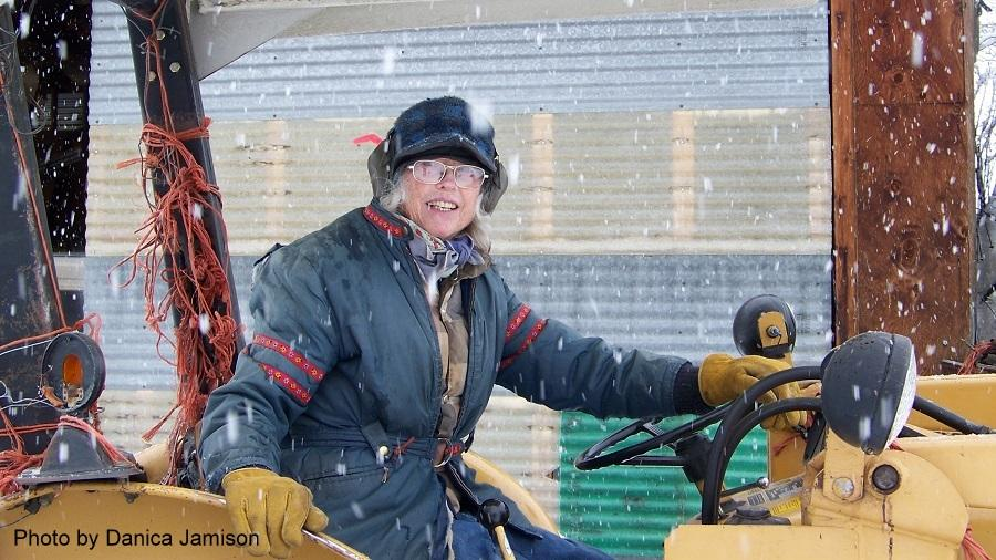 female driving tractor in winter with snow falling