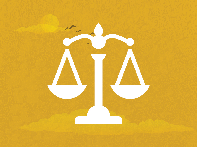 Image of justice scales on a golden sky background.