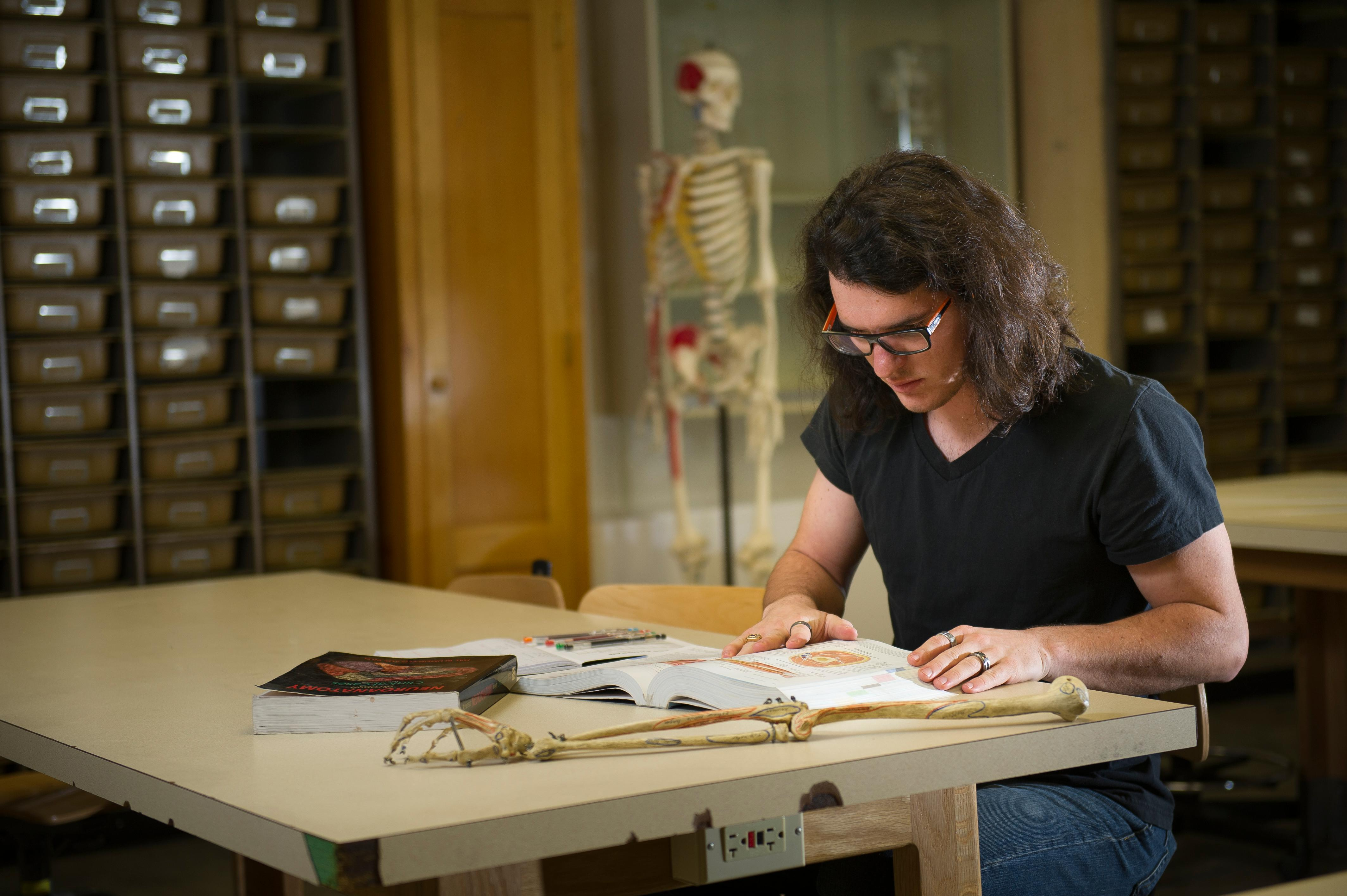 Male student studying next to a skeleton