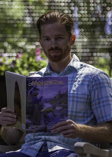 Casey Pallister holding an issue of Montana, the magazine of western history