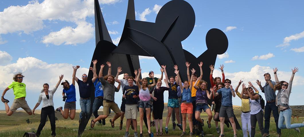 Students jumping excitedly in front of a modern metal sculpture