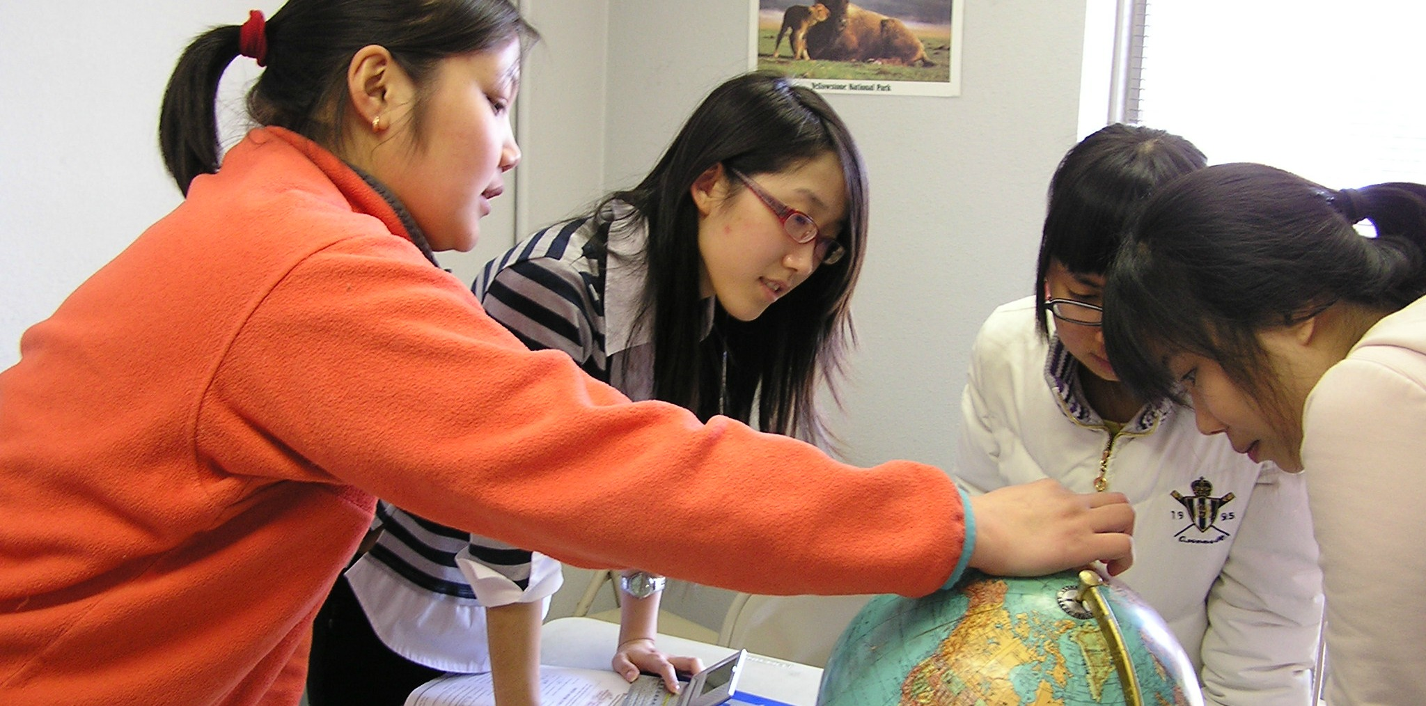 International Students looking at a globe