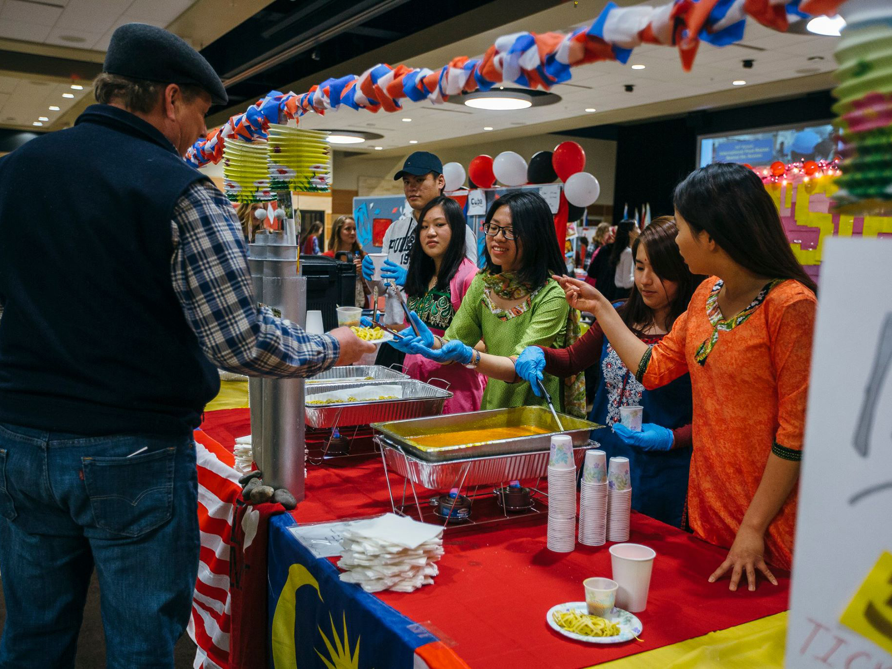 Students serving food at 34th Annual Interntional Food Bazaar