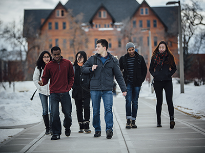 Students walk down the hill from Montana Hall