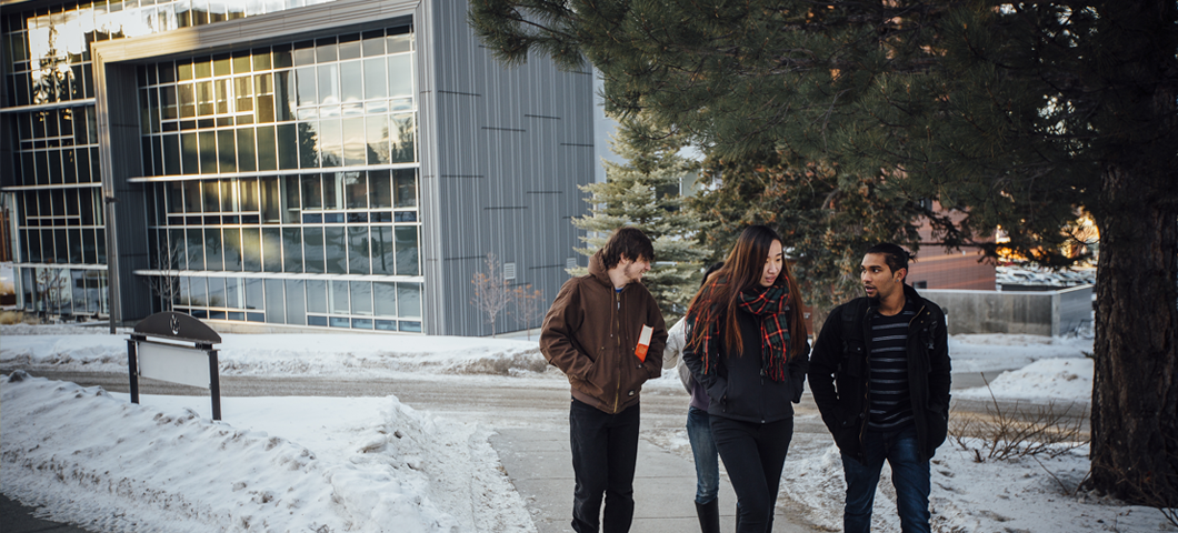 Four international students walking in front of Jake Jabs Hall