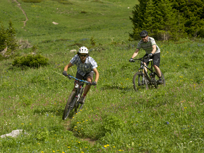 Two mountain bikers biking through the grass in Bozeman.
