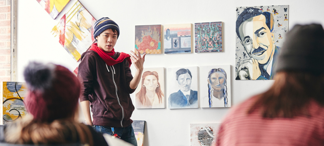 Student standing at the front of a class with art hanging on the wall