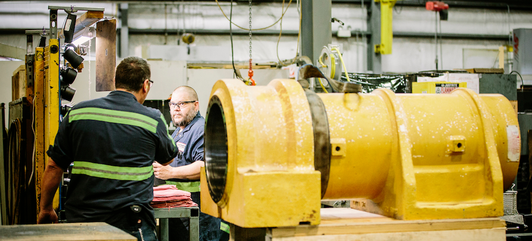 Two workers at manufacturing plan with large yellow metal part in foreground
