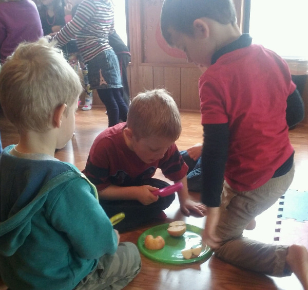 children investigating apple slices with magnifying glasses