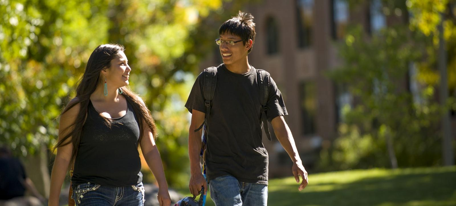 two native american students walking through campus in the afternoon