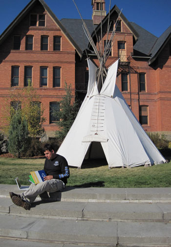 Native American Student sitting in front of tipi