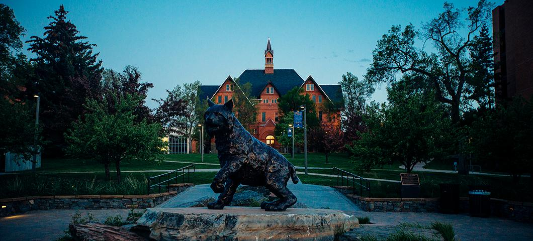 Photo of Montana Hall and Spirit statue at dusk