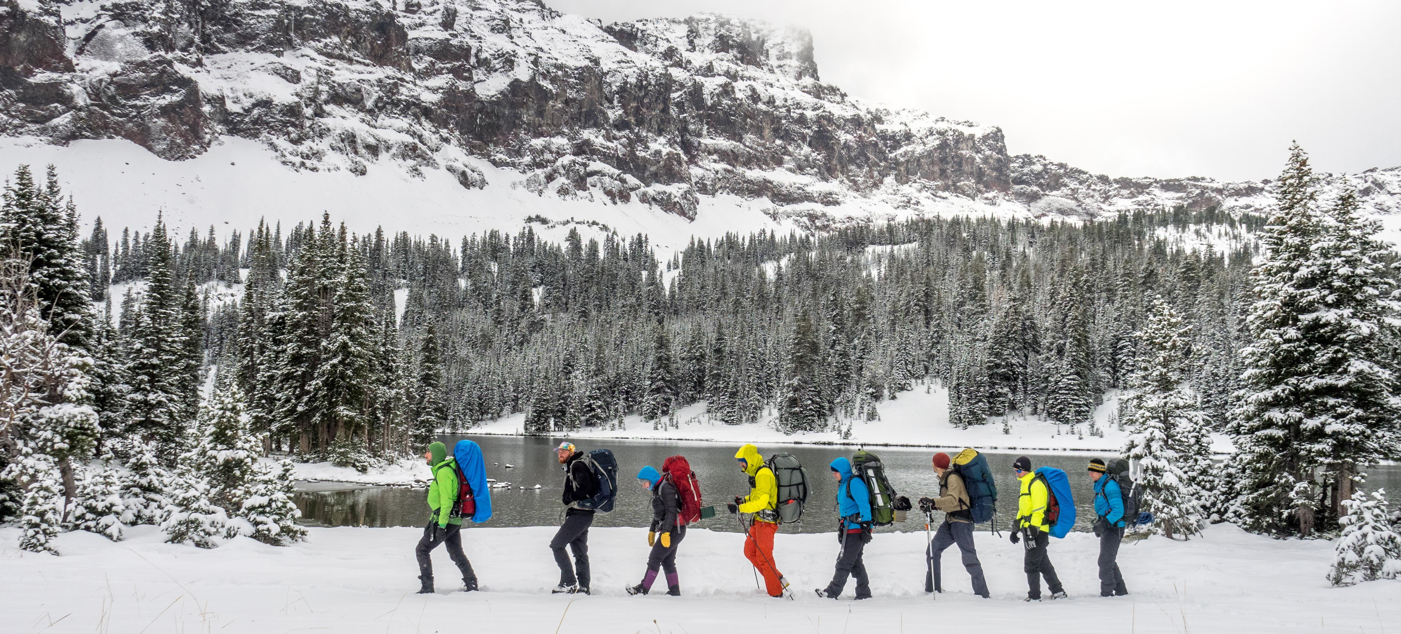 Group of winter enthusiasts hiking in a snowcovered, mountain meadow.