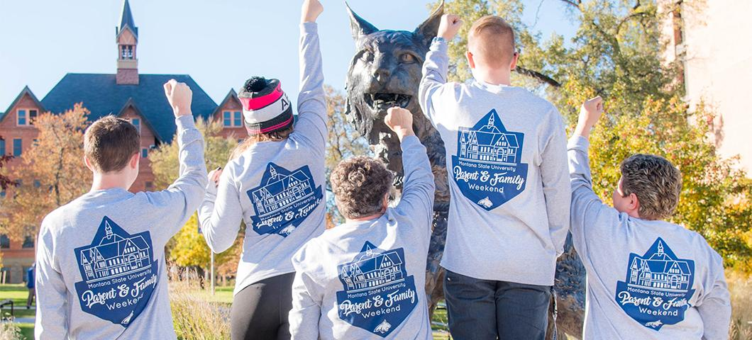 A family poses next to the Spirit statue in their parent & family weekend shirts