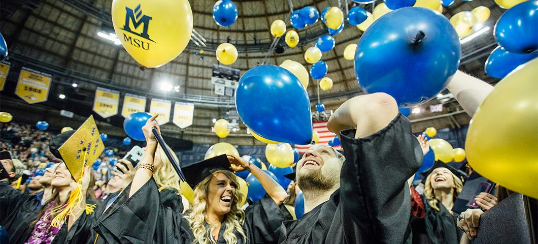 Student celebrate under balloons at Commencement ceremonies