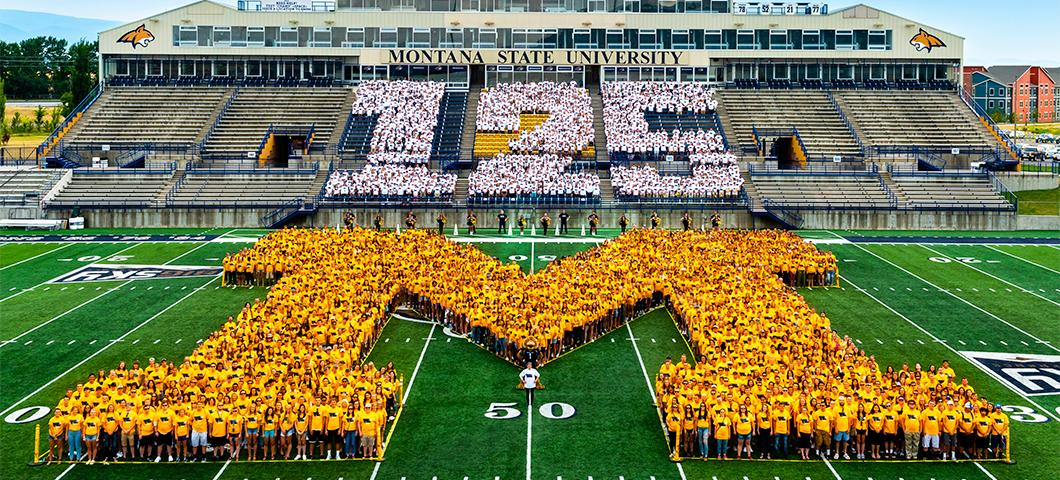The greater MSU and Bozeman community make out the number '125' alongside the incoming freshman 'M' on the football field