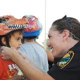 police helping child put a helmet on for safety