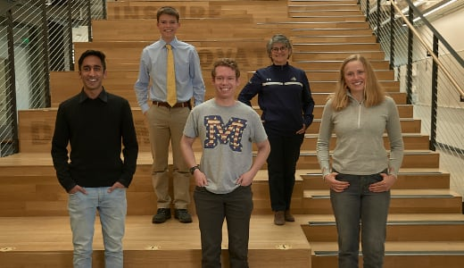 Five people pose on a set of stairs.