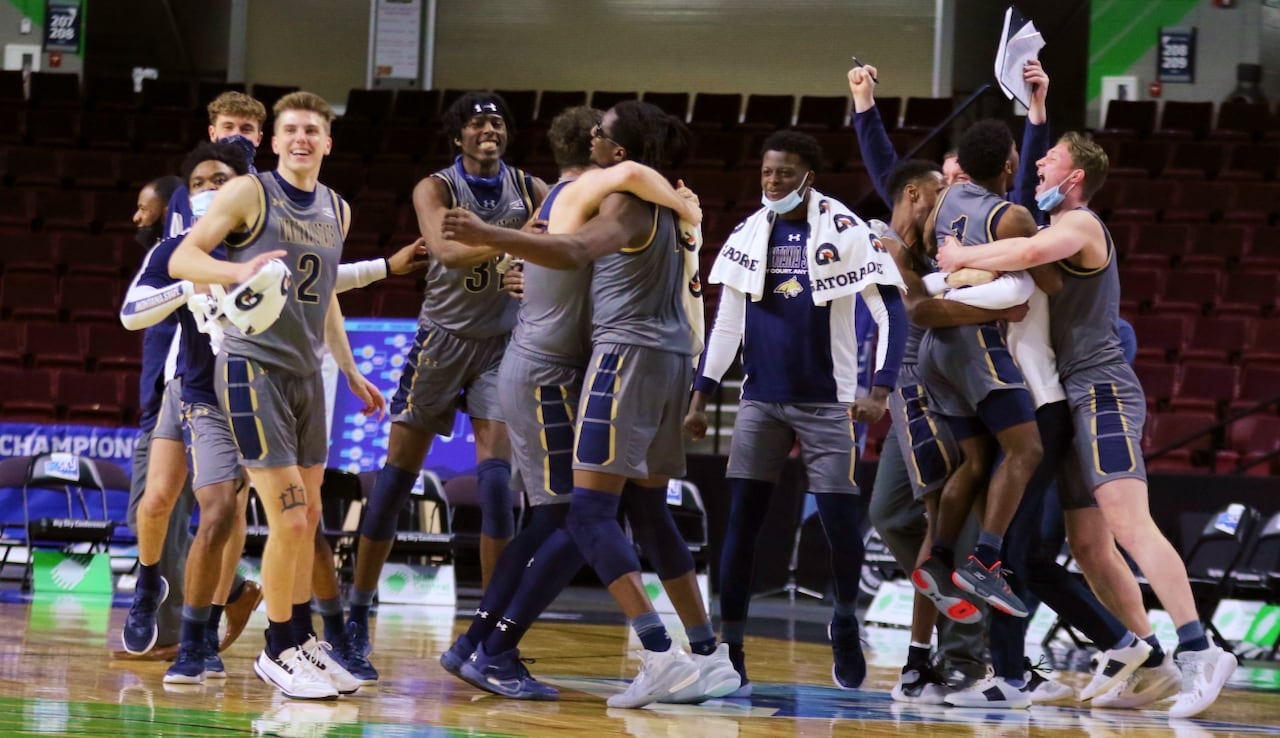 Members of a men's basketball team celebrate on a basketball court.