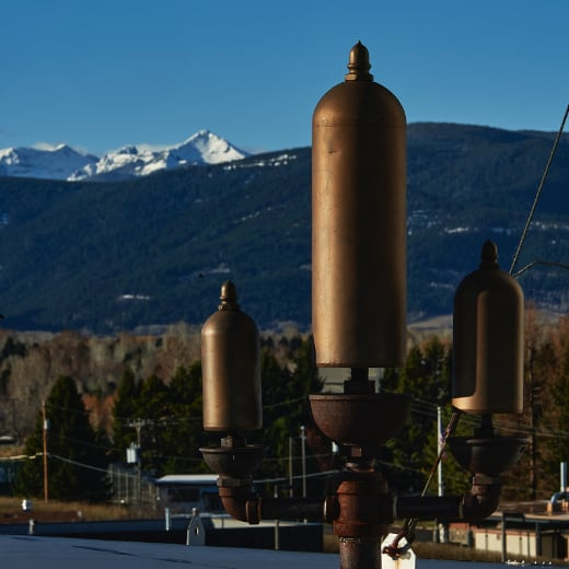 A steam whistle on top of a building with mountains in the background.