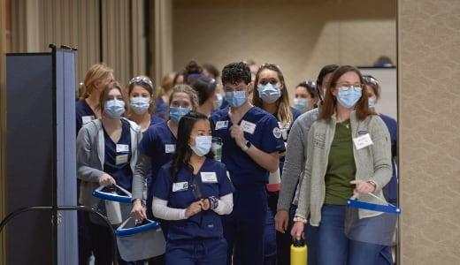 A group of people in nursing scrubs walks through a wide doorway.