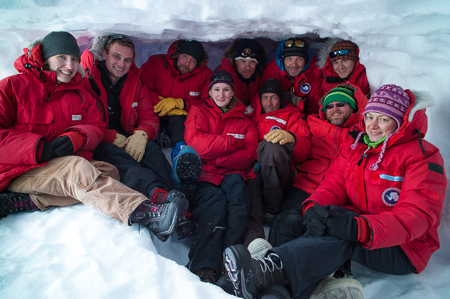 team in red under ice cave