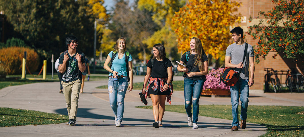 A group of students walk across campus in fall.