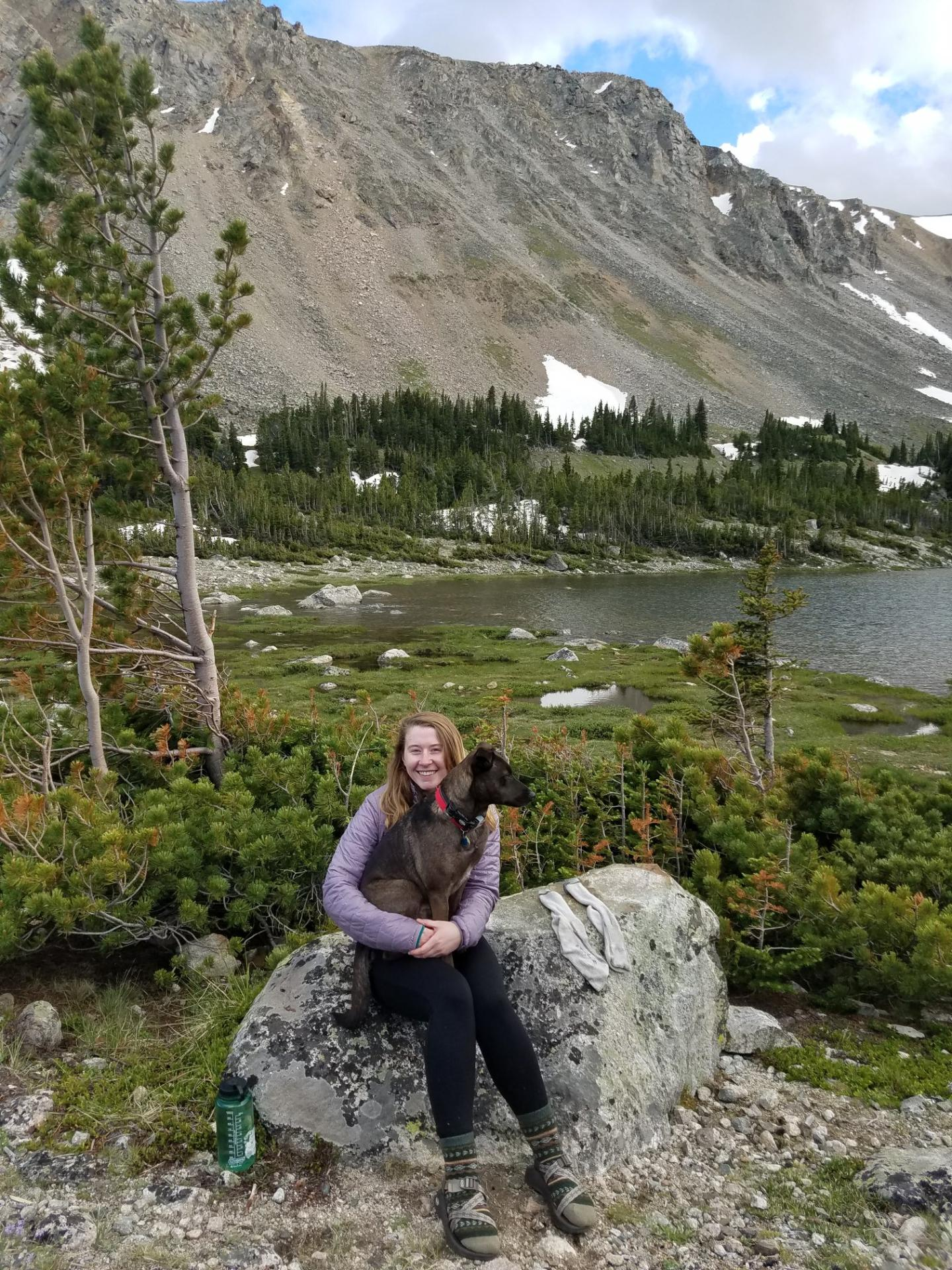 Picture of Katelynne Cowart sitting on a rock with mountain in background