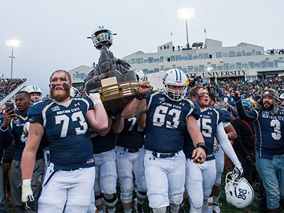MSU football players carrying the Great Divide trophy after winning the 2017 Brawl of the Wild vs. U Montana