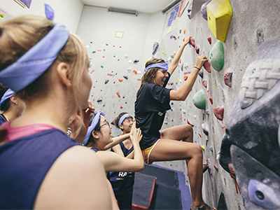 Female student on the climbing wall at the fitness center