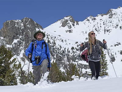 Male and female student snowshoeing on a mountain