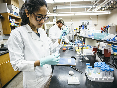 Female student conducting chemical engineering research in a lab