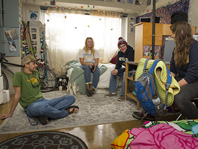 Four students hanging out in a dorm room