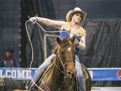 Female rider lassoing at rodeo