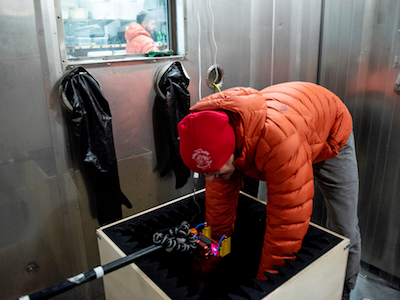 MSU student in puffy orange coat bending over to handle experiment in dark box inside freezer chamber