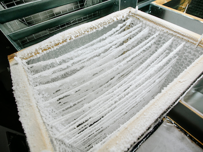 close-up photo pf strings holding snow crystals in a snow-making device
