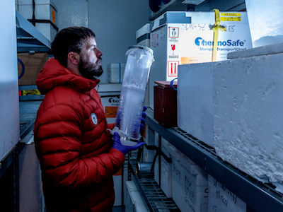 MSU researcher in orange puffy coat handling cylindrical ice core sample