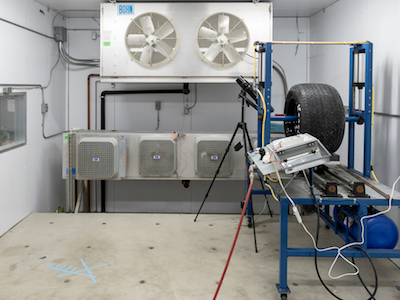 cold room with concrete floor, including experiment in which blue rack holds car tire that spins
